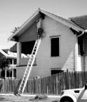 Un homme peint sa maison